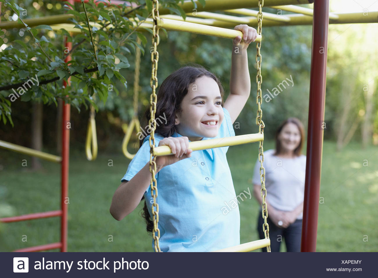 Young girl outdoors at playground climbing with senior woman in background smiling - Stock Image