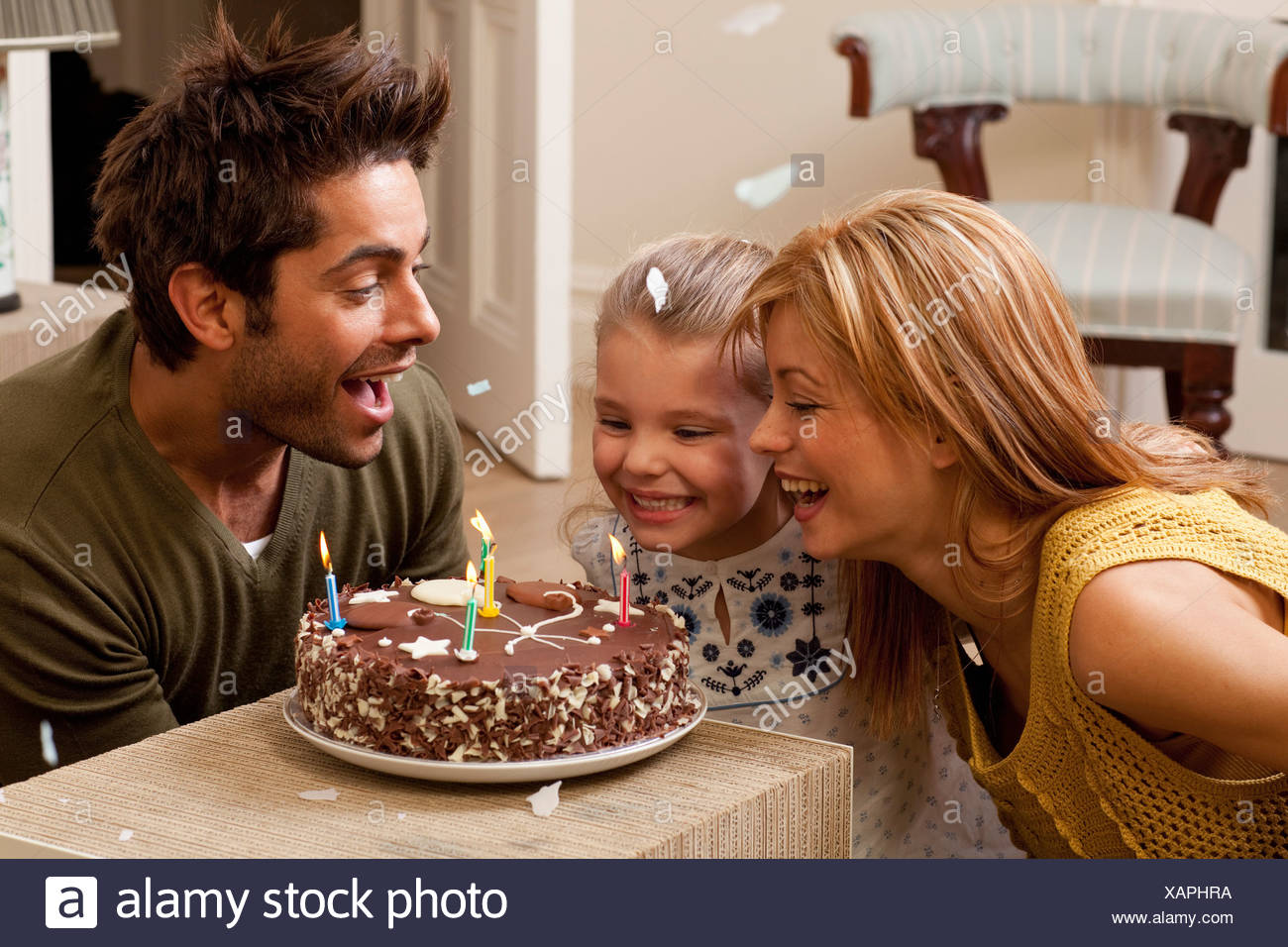 parents and child blowing out candles - Stock Image