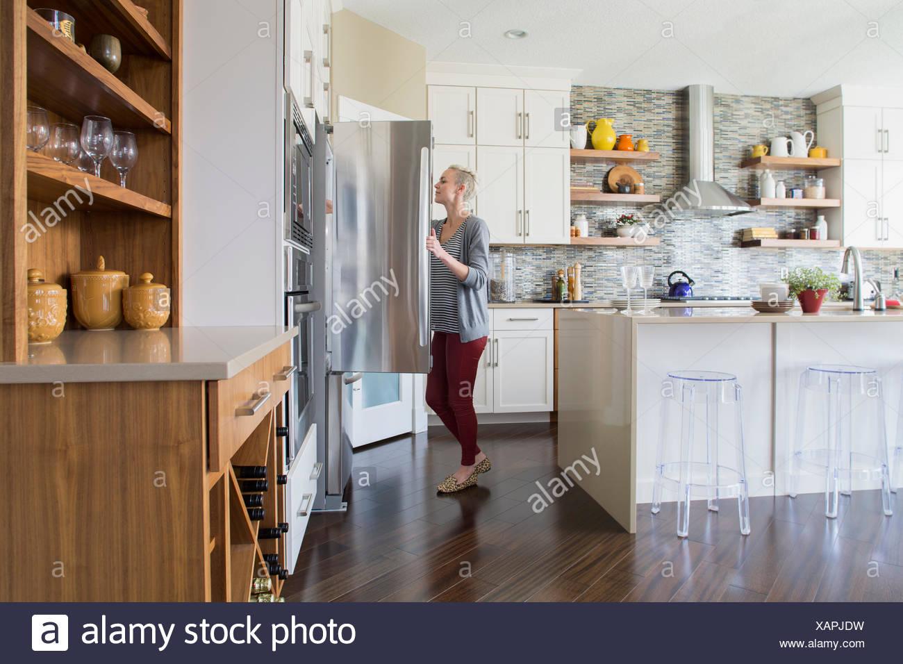 Woman opening refrigerator door in kitchen - Stock Image