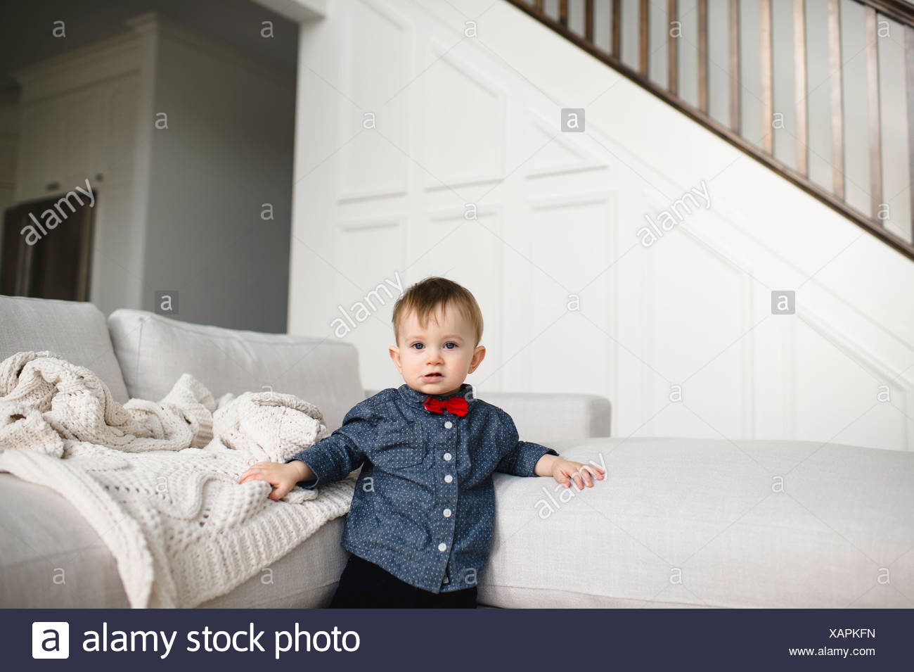 Portrait of male toddler in red bow tie leaning against sofa - Stock Image