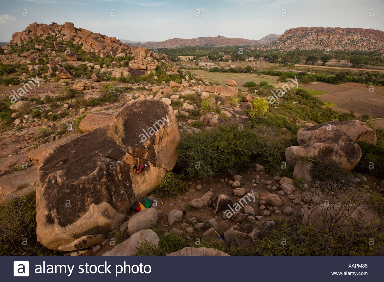 Female climber alone on a massive boulder amid a landscape of stone and brush. - Stock Image