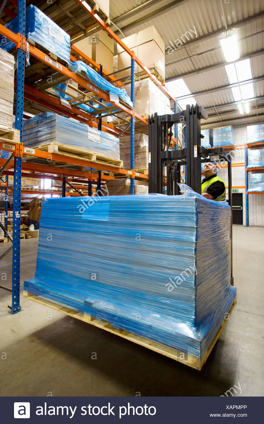 Warehouse worker moving boxes on pallet with forklift - Stock Image