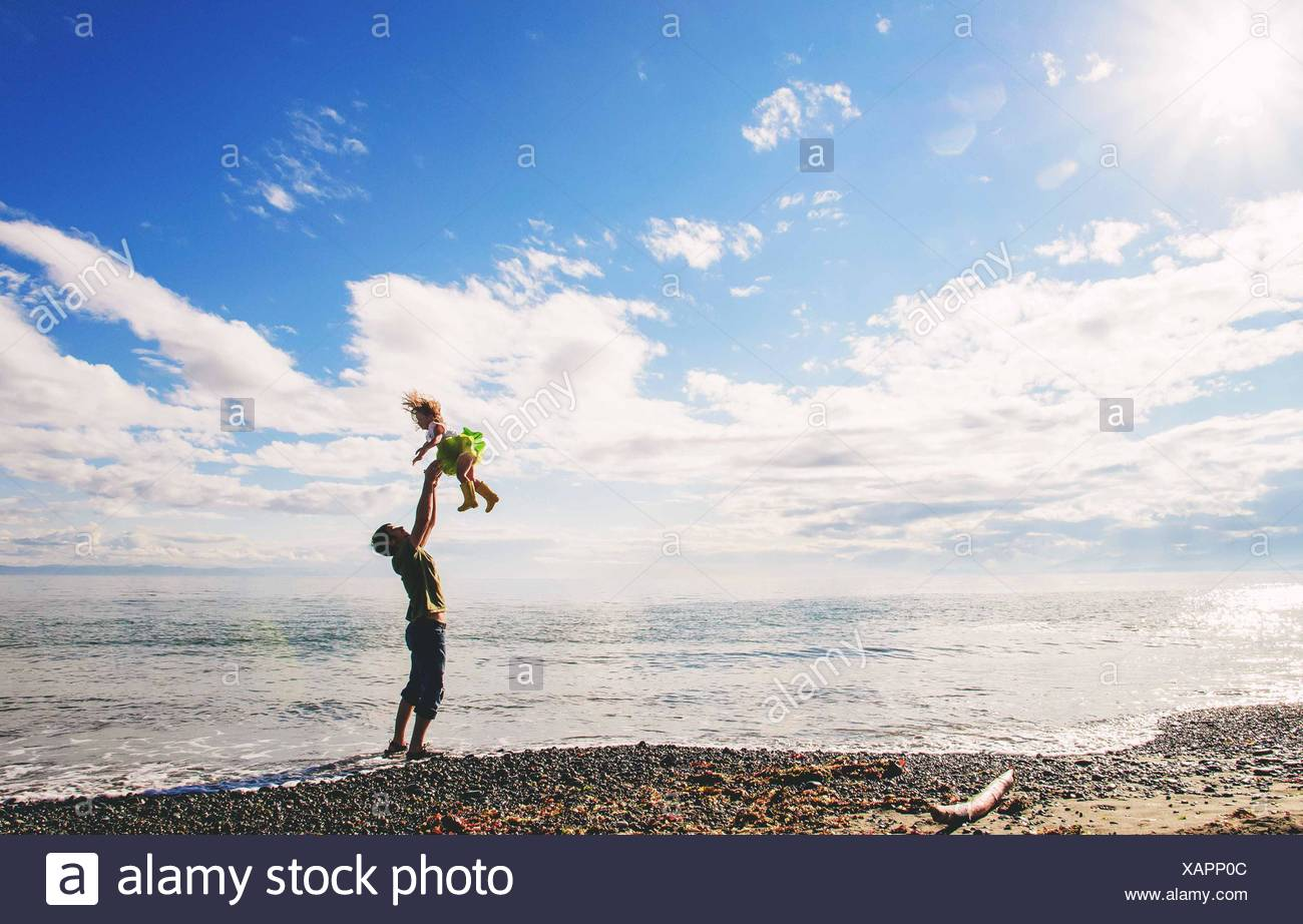 Father throwing little girl (2-3) up in air on beach - Stock Image