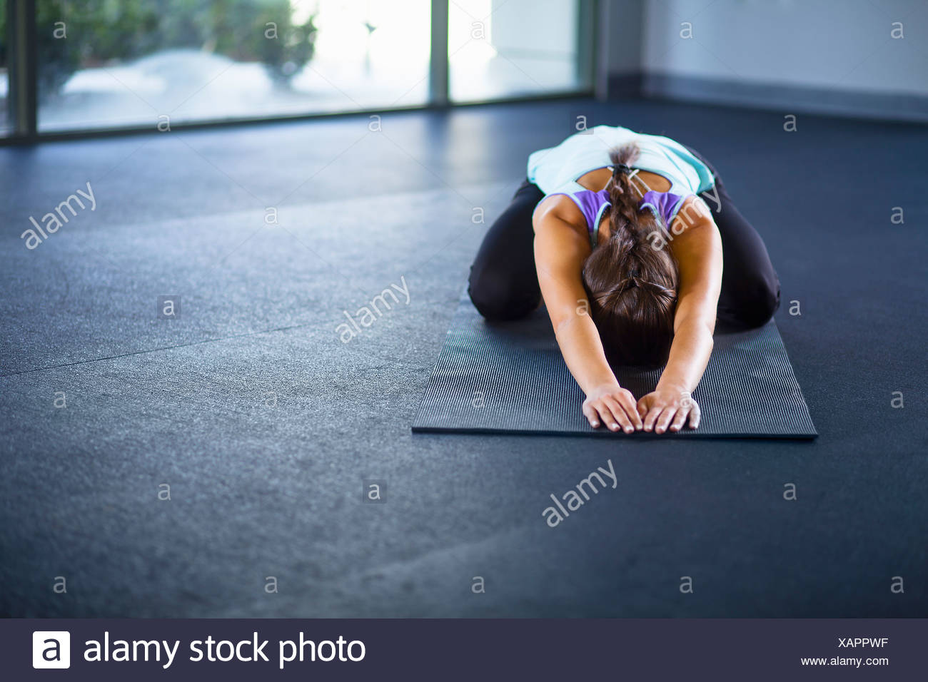 Young woman in tortoise pose - Stock Image
