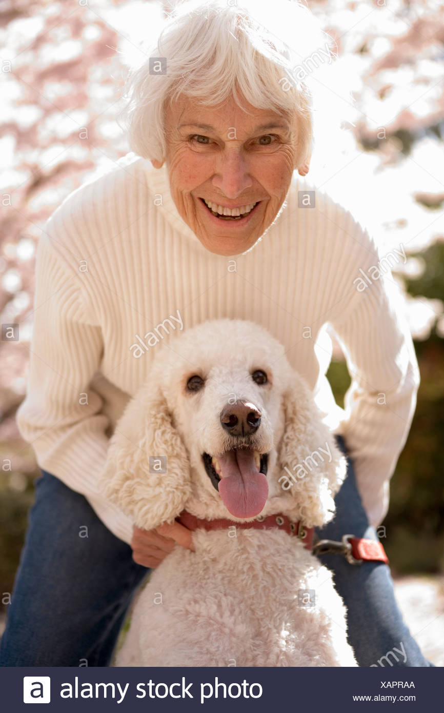 Portrait of senior woman with dog - Stock Image