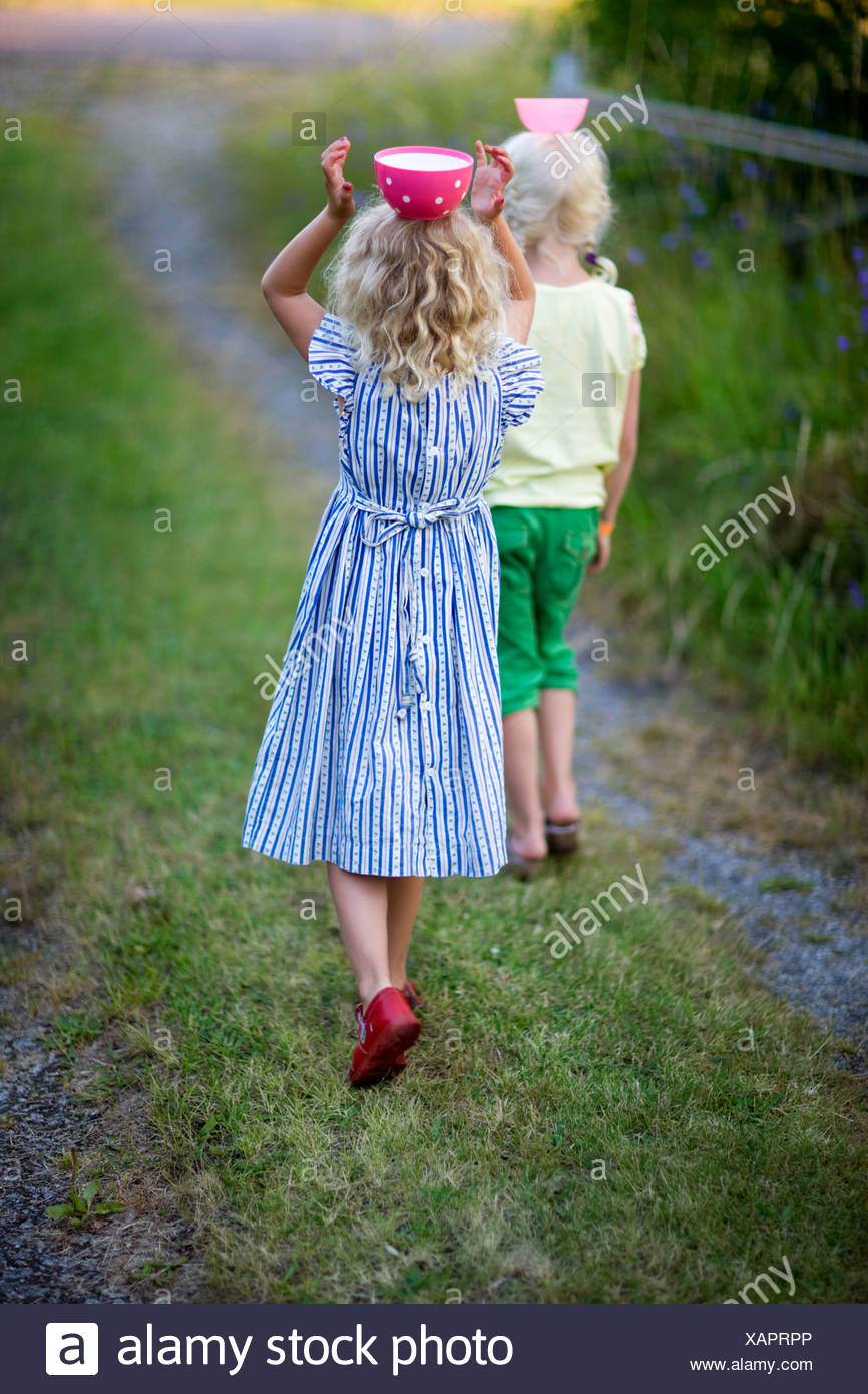 Girls carrying bowls on heads - Stock Image
