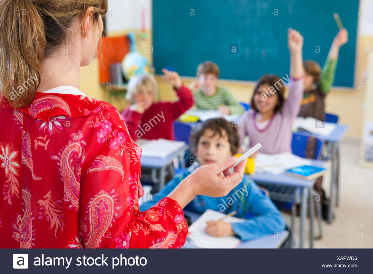 Over the shoulder view of primary school teacher questioning in classroom - Stock Image