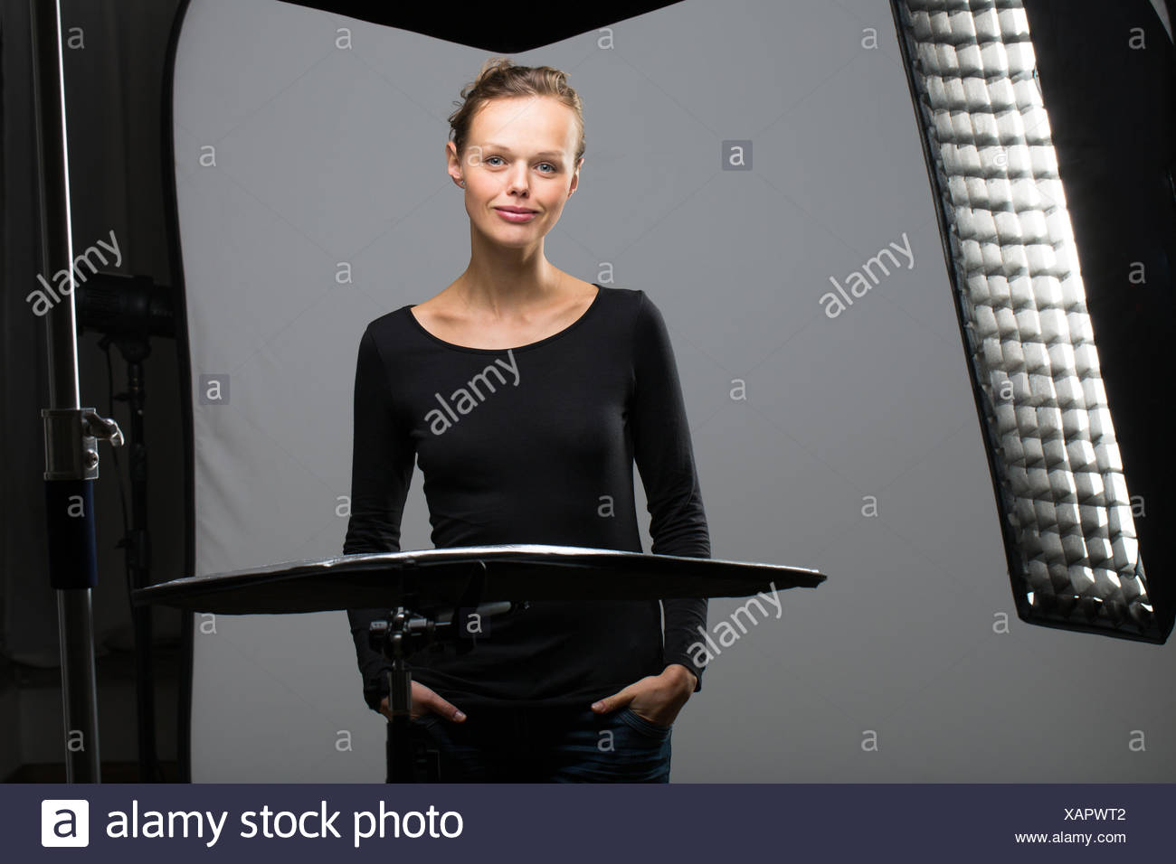 Beautiful female model posing in a photographic studio surrounded by professional strobe lights Stock Photo