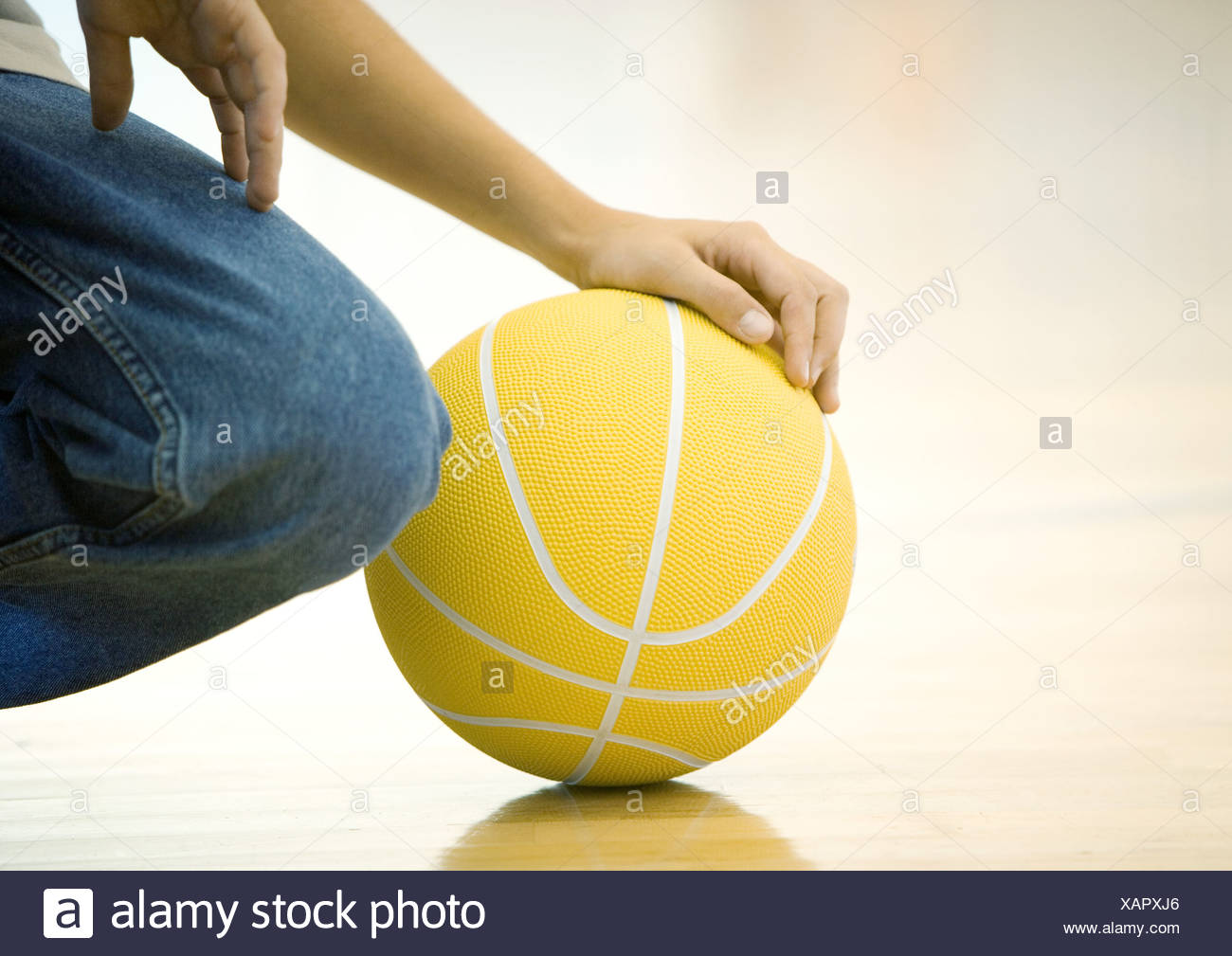 Teen boy crouching, holding basketball, close-up of hand on ball and knee - Stock Image