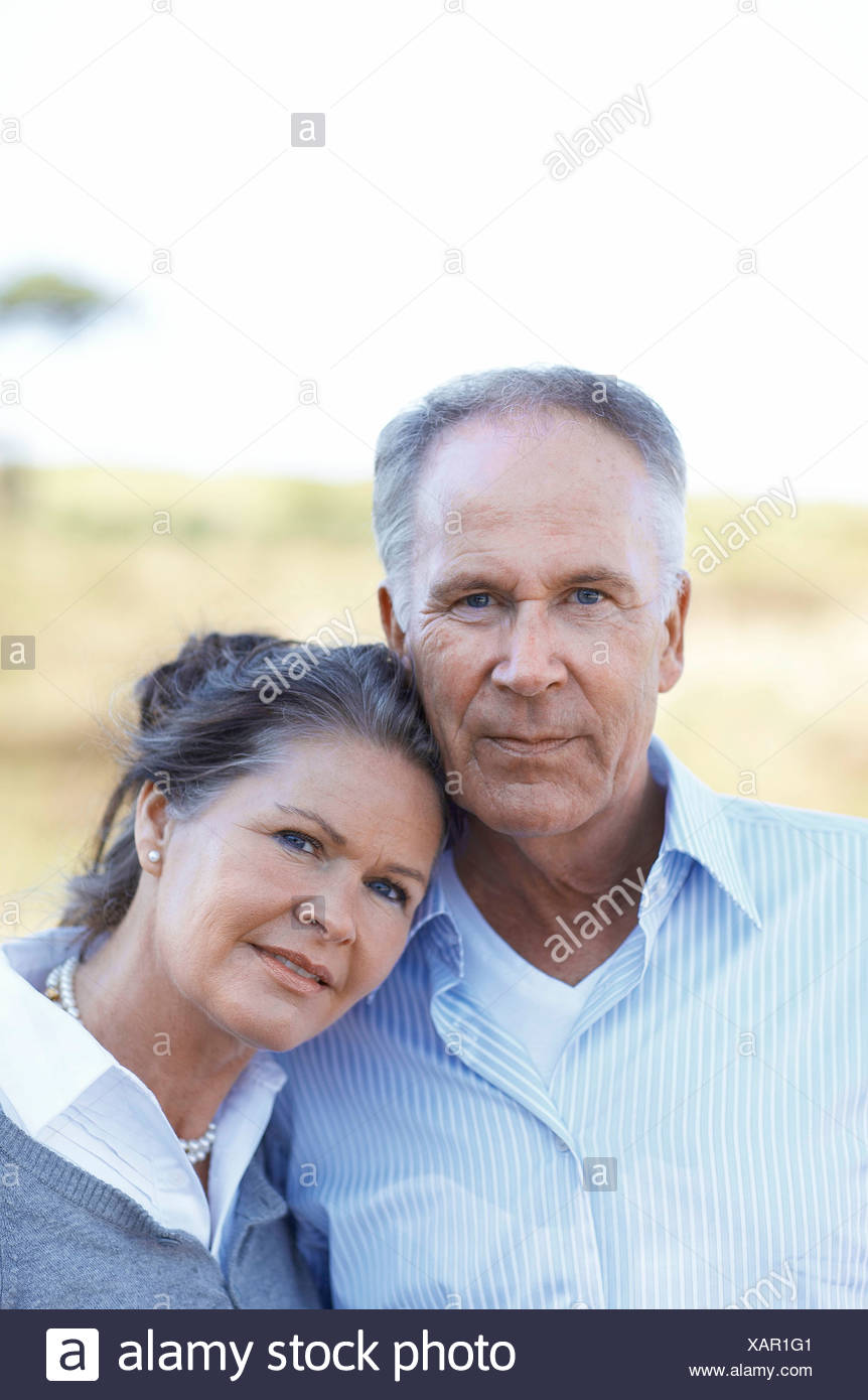 Mature couple standing close together - Stock Image