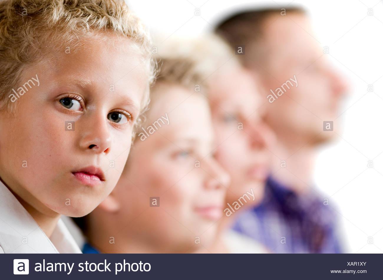 Seitenansicht einer Familie mit zwei halbwüchsigen Söhnen. Jüngster Sohn im Fokus blickt ernst in die Kamera. - Stock Image