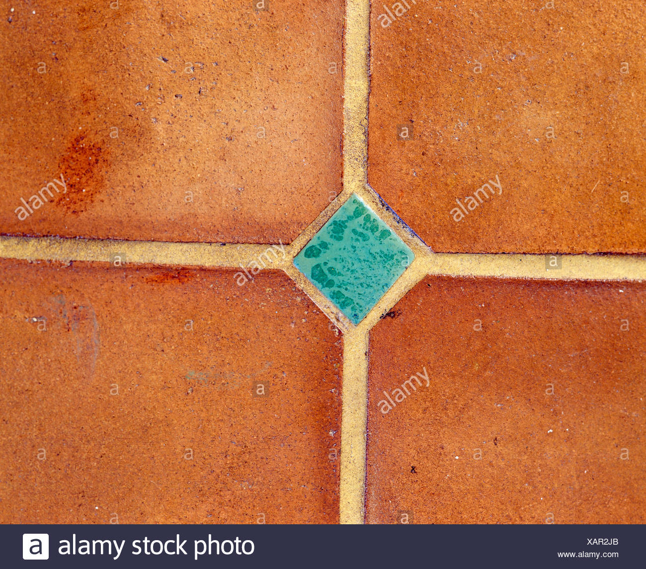 Close-up of terracotta floor tiles with turquoise insert
