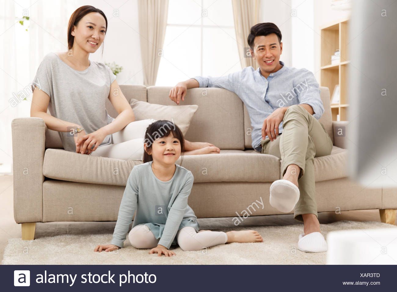 A happy family of three in the living room watching TV Stock ...