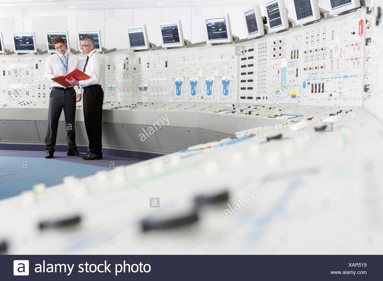 Engineers discussing paperwork in control room of nuclear power station - Stock Image