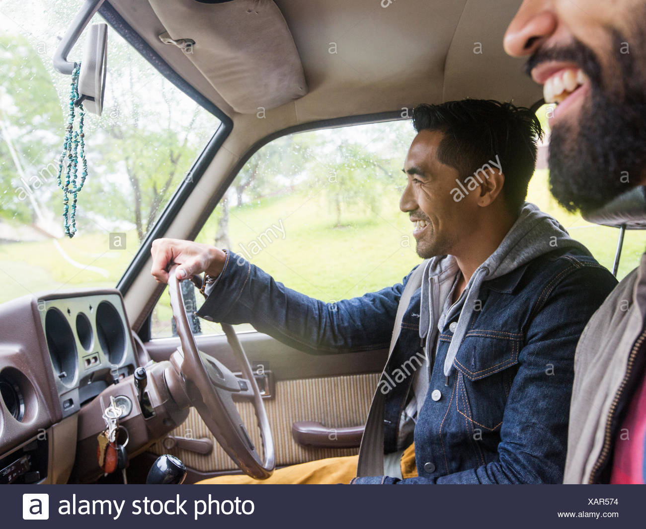 Two young men in a car, driver and passenger, smiling - Stock Image