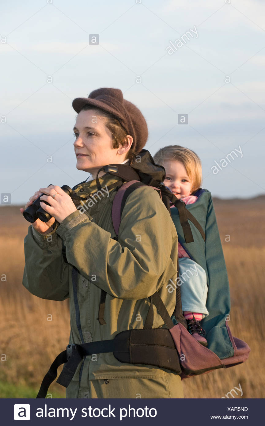 ccbfc32ffb mother carrying toddler in backpack while bird watching along coastal path  North Norfolk winter - Stock