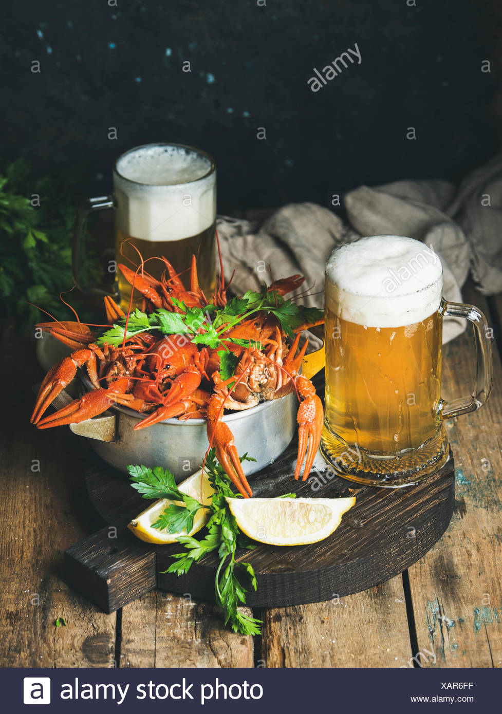 Two pints of wheat beer and boiled crayfish with lemon and parsley on dark round serving board over rustic wooden background, se - Stock Image