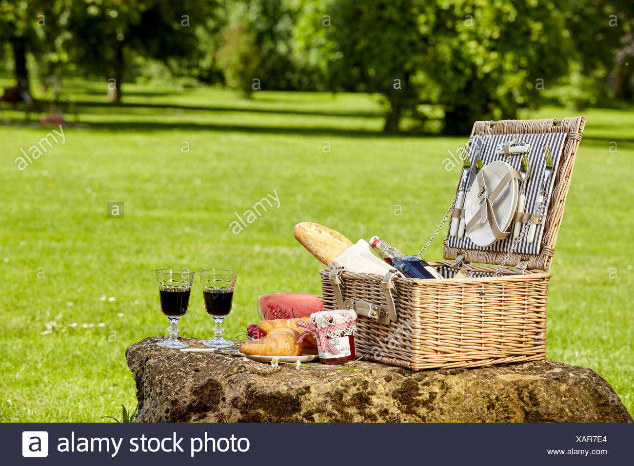 Fitted Stylish Wicker Picnic Hamper With Red Wine In Wineglasses Jam And Fresh Bread On A Rock In A Sunny Lush Green Park With Copy Space Stock Photo Alamy