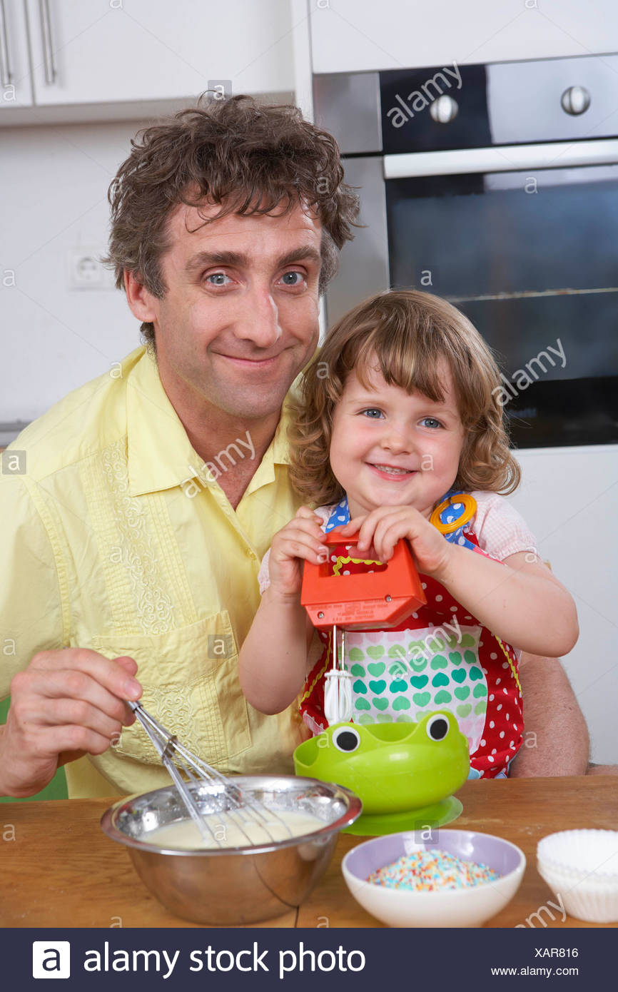 Father and daughter, stirring batter Stock Photo