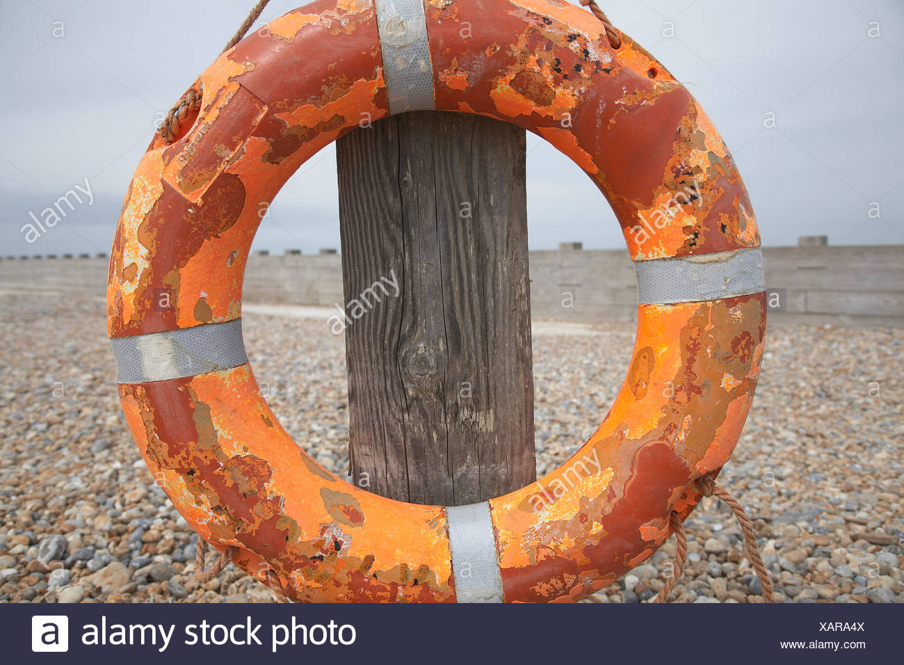 Lifebuoy attached to wooden post on beach in England - Stock Image