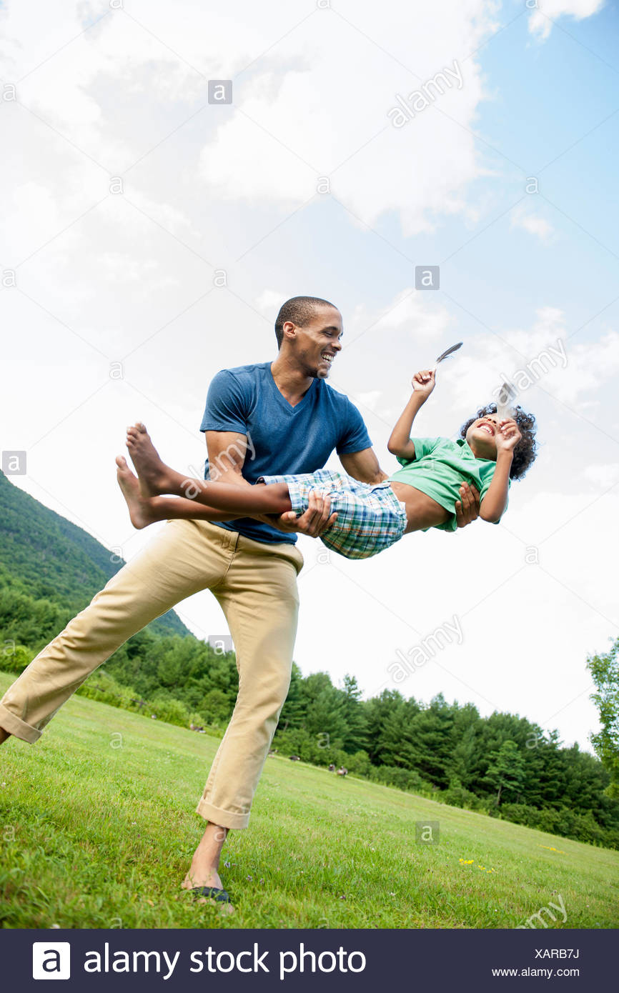 A man lifting his son up in his arms, playing outdoors. - Stock Image