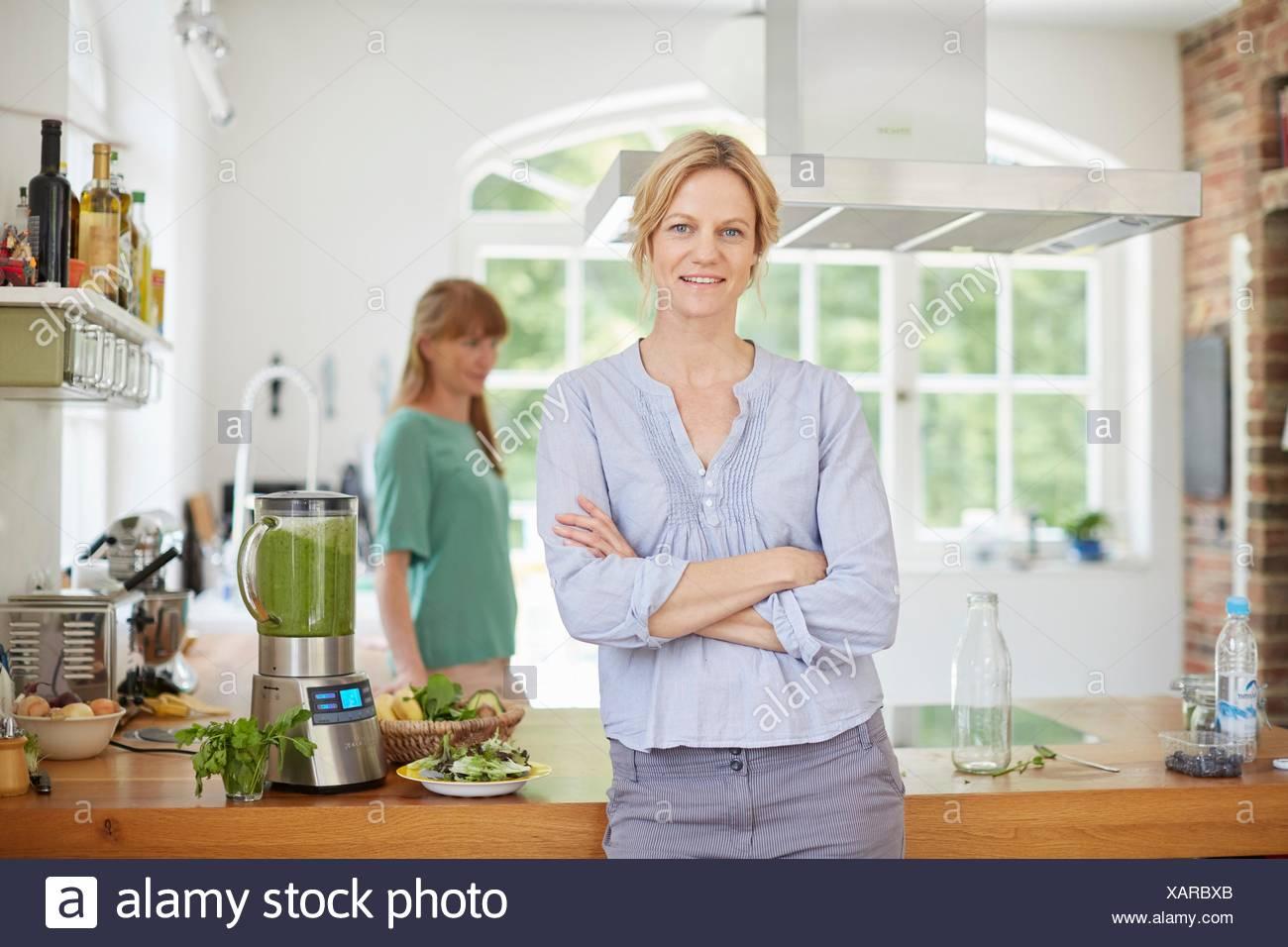 Women next to blender full of green vegan smoothie - Stock Image