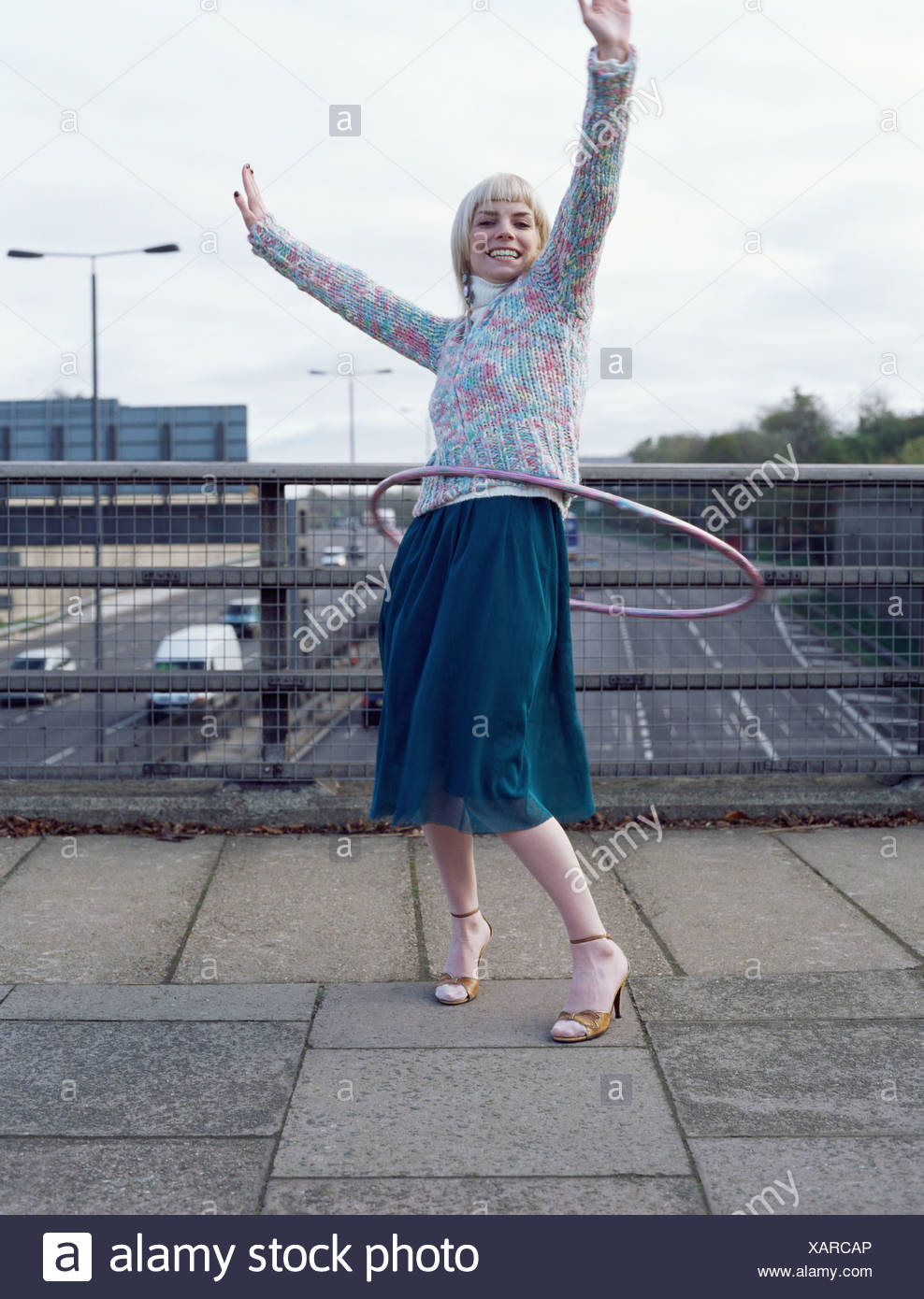 Woman playing with hula hoop on motorway bridge - Stock Image