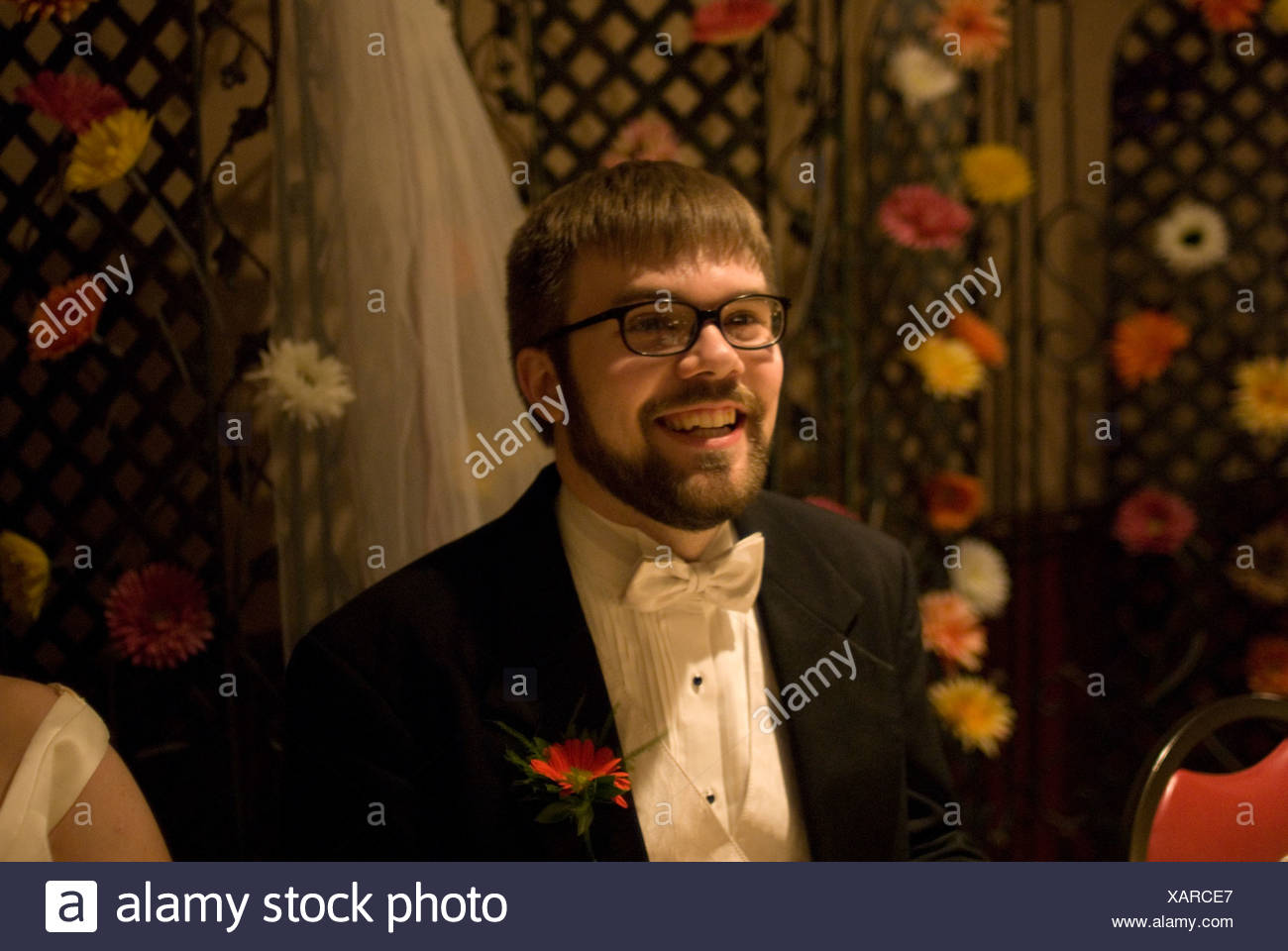 A man in a tux smiles on his wedding day. - Stock Image