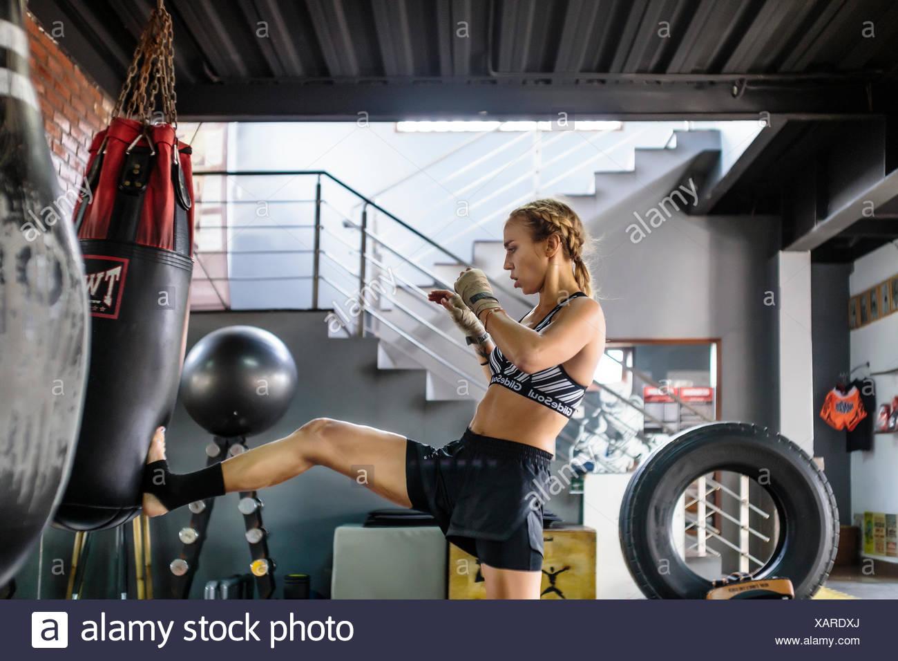 Side view photograph of female kickboxer kicking punching bag, Seminyak, Bali, Indonesia Stock Photo