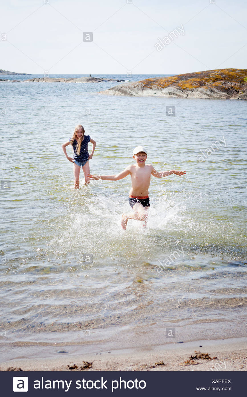 Children (8-9) bathing in sea - Stock Image