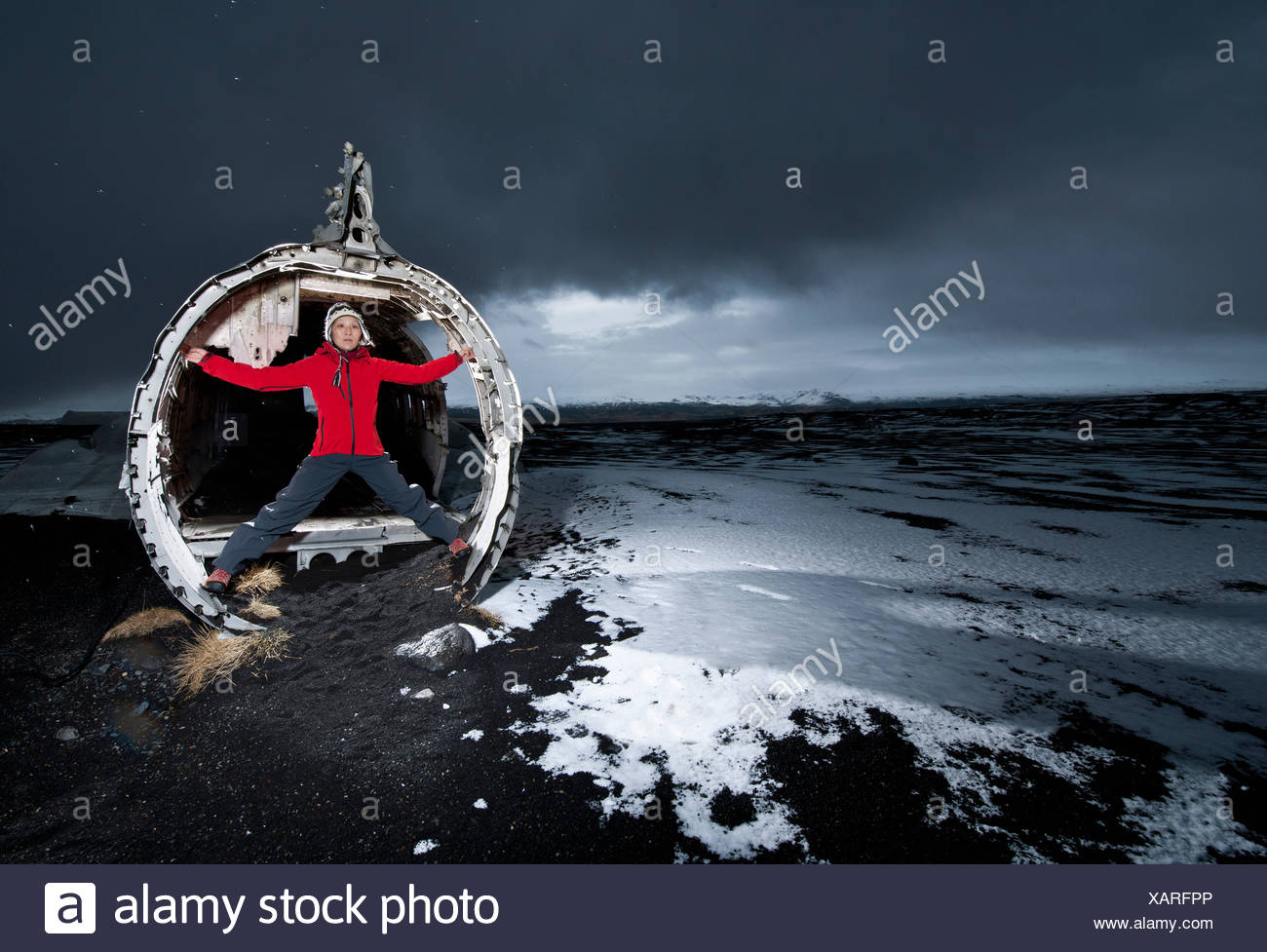 Hiker standing in airplane wreck in snow - Stock Image