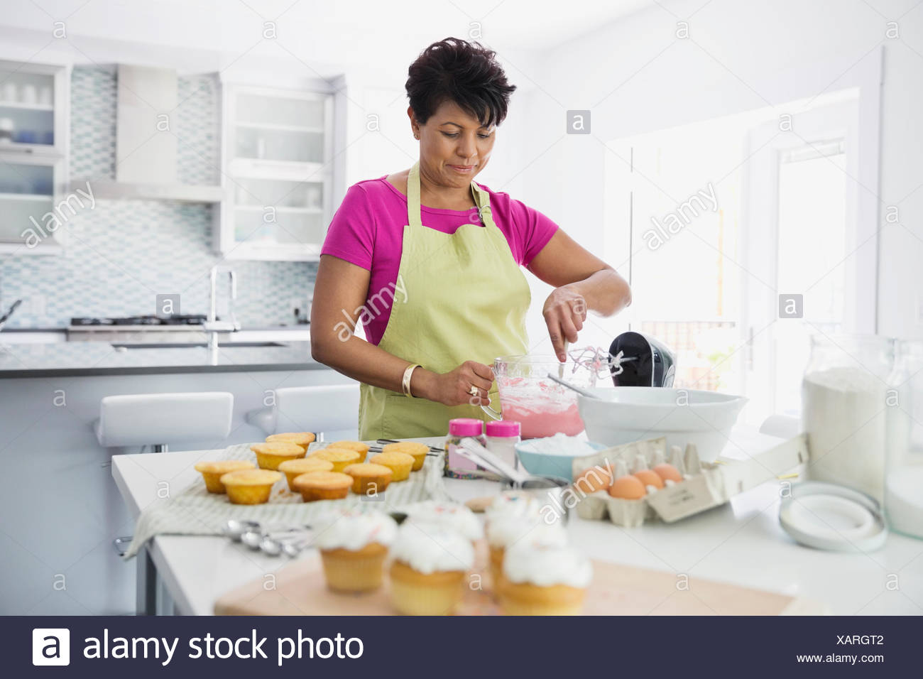 Woman mixing ingredients in bowl to decorate cupcakes - Stock Image