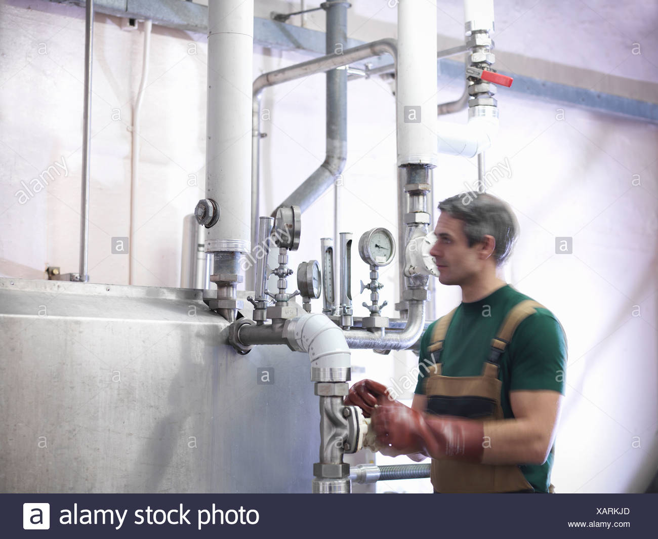 Worker turning valve in brewery - Stock Image