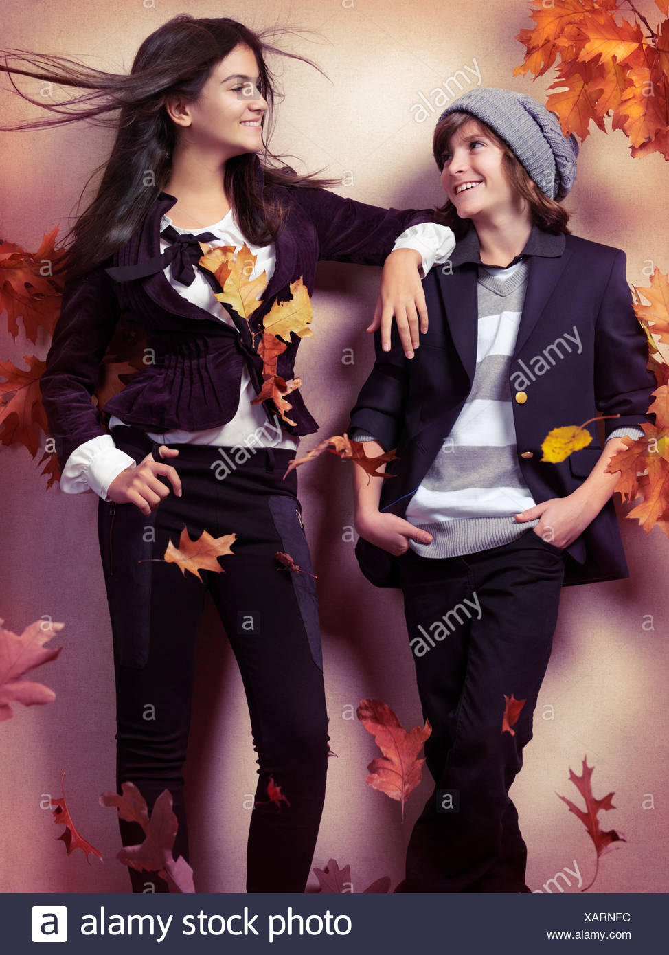 A Smiling Boy And A Teenage Girl Wearing Fashionable Clothes Autumn Leaves Falling Around Them Stock Photo Alamy