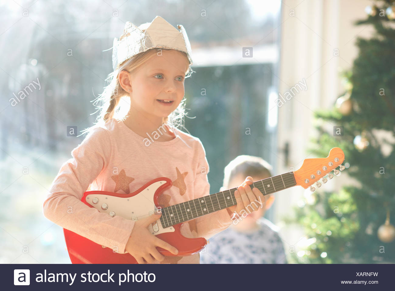 Girl playing with toy guitar on christmas day - Stock Image