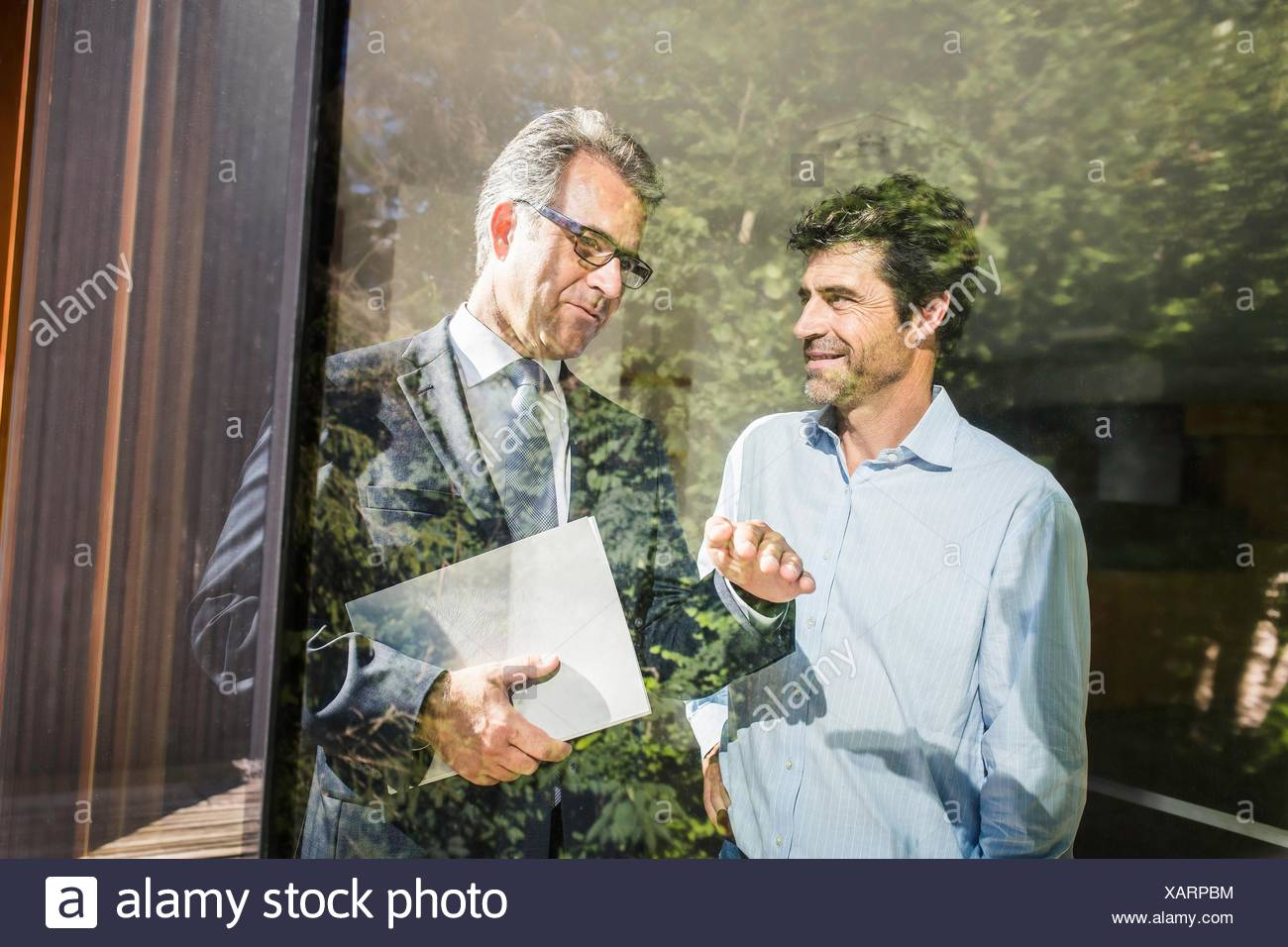 Estate agent showing mature man around new house - Stock Image