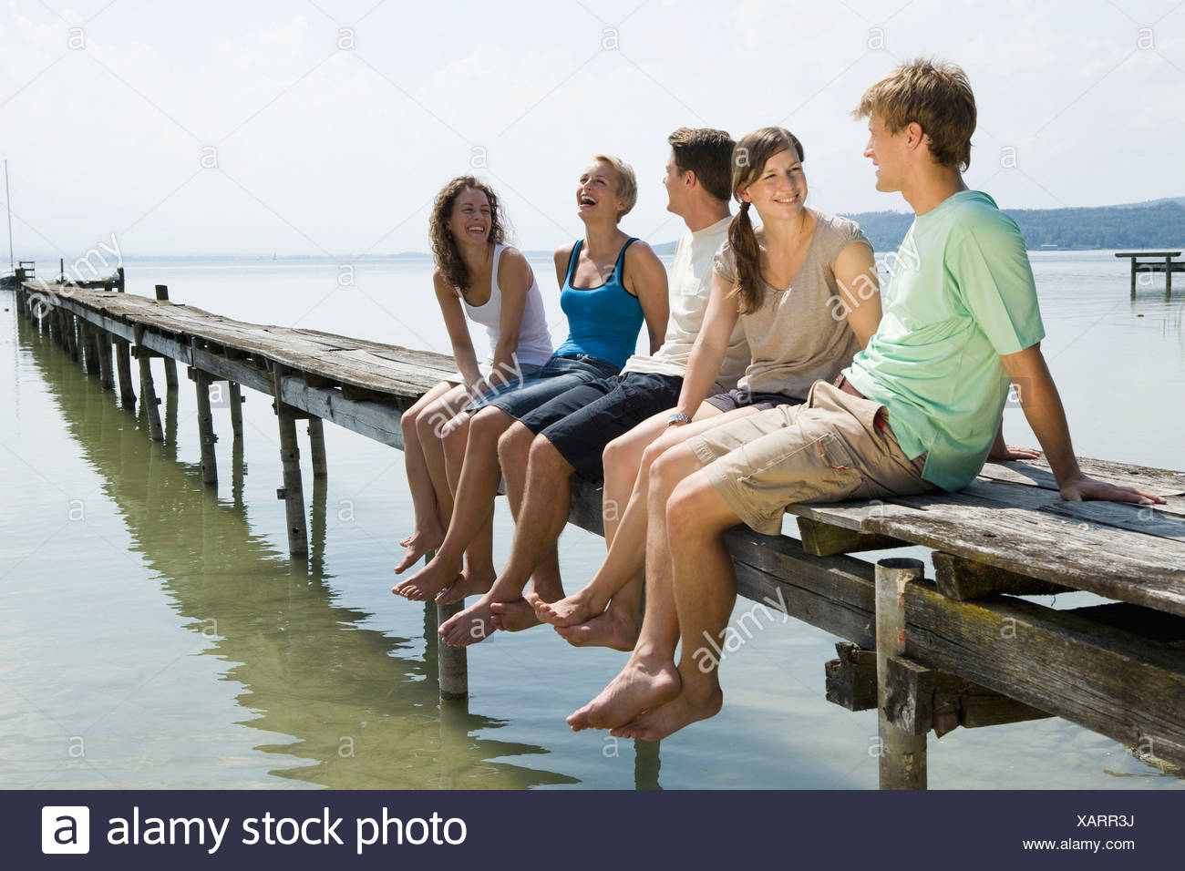 Germany, Bavaria, Ammersee, Young people relaxing on jetty - Stock Image