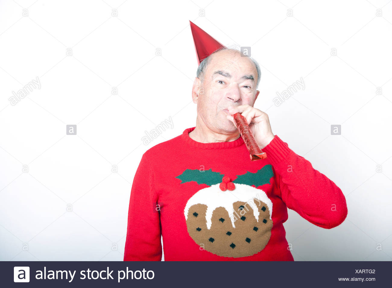 Senior adult man wearing Christmas jumper blowing party blower - Stock Image