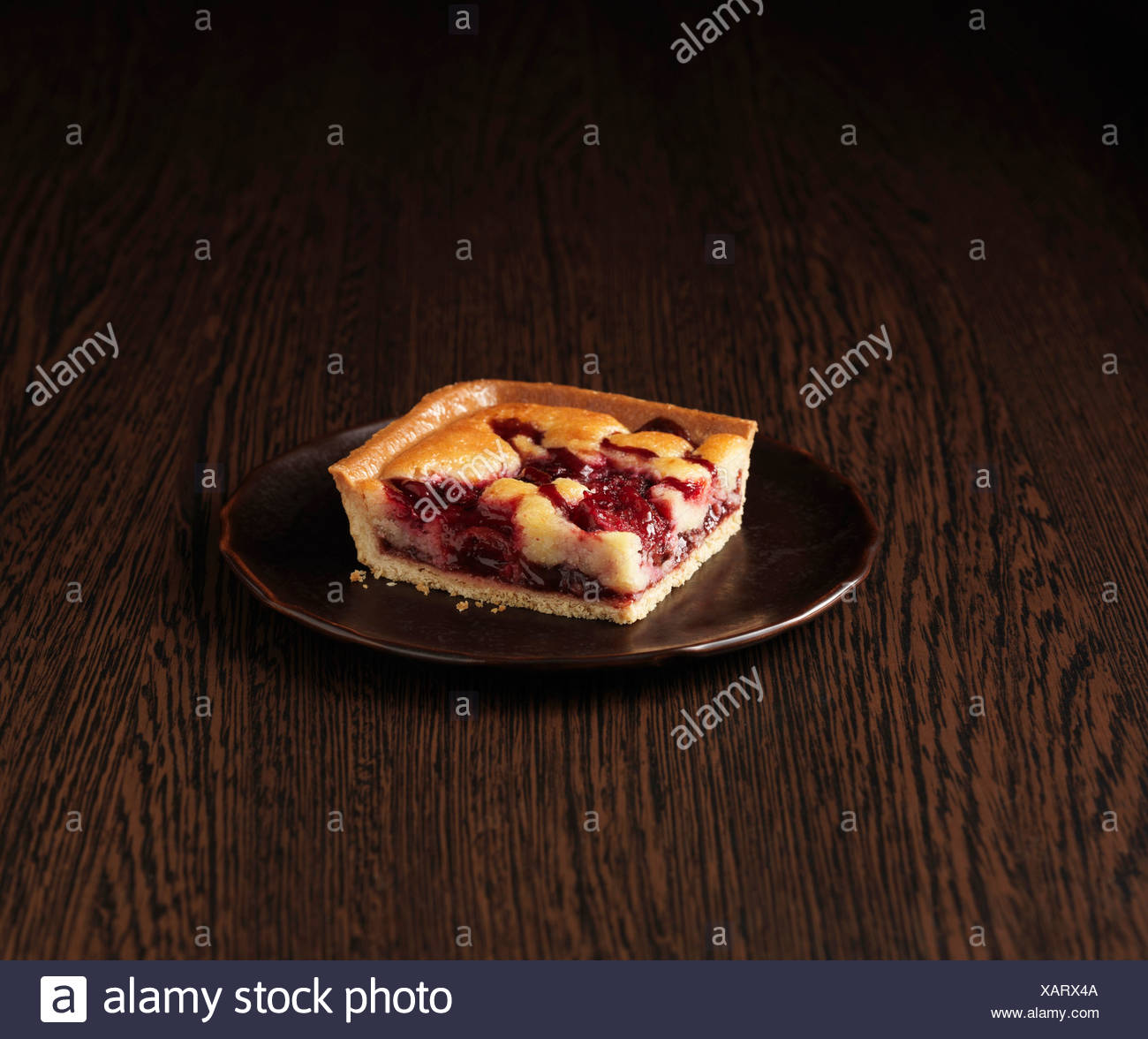 Slice of morello cherry frangipane tart - Stock Image