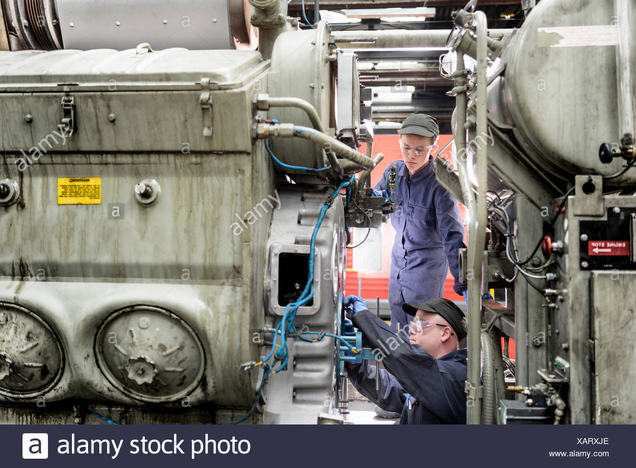 Apprentice watching engineer working on locomotive engine in train works - Stock Image