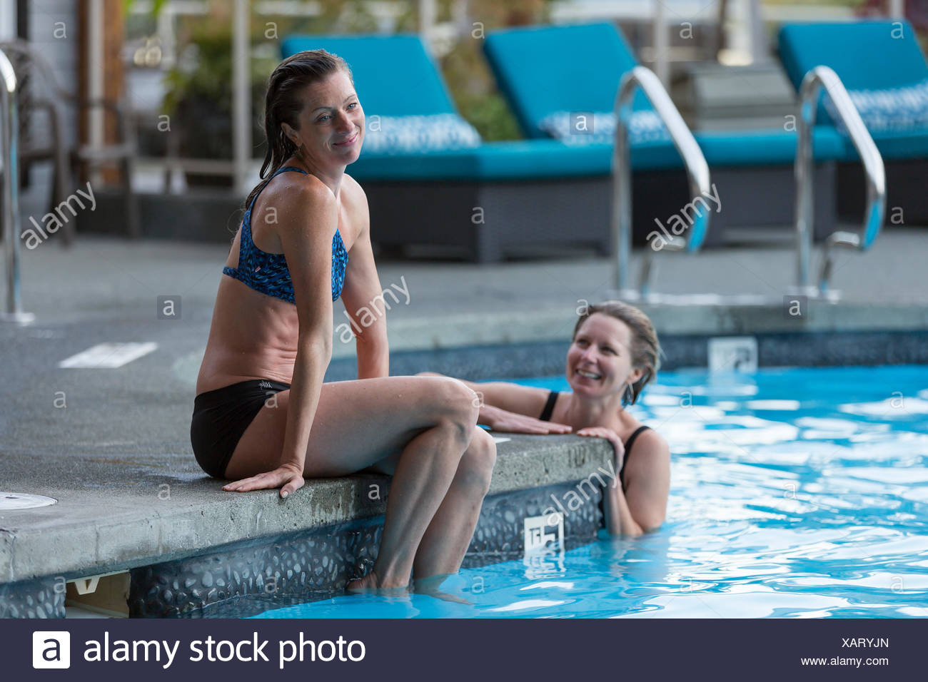 Two girlfriends relax at the outdoor pool while visiting the Kingfisher Resort and spa.  The Comox Valley, Vancouver Island, British Columbia, Canada Stock Photo