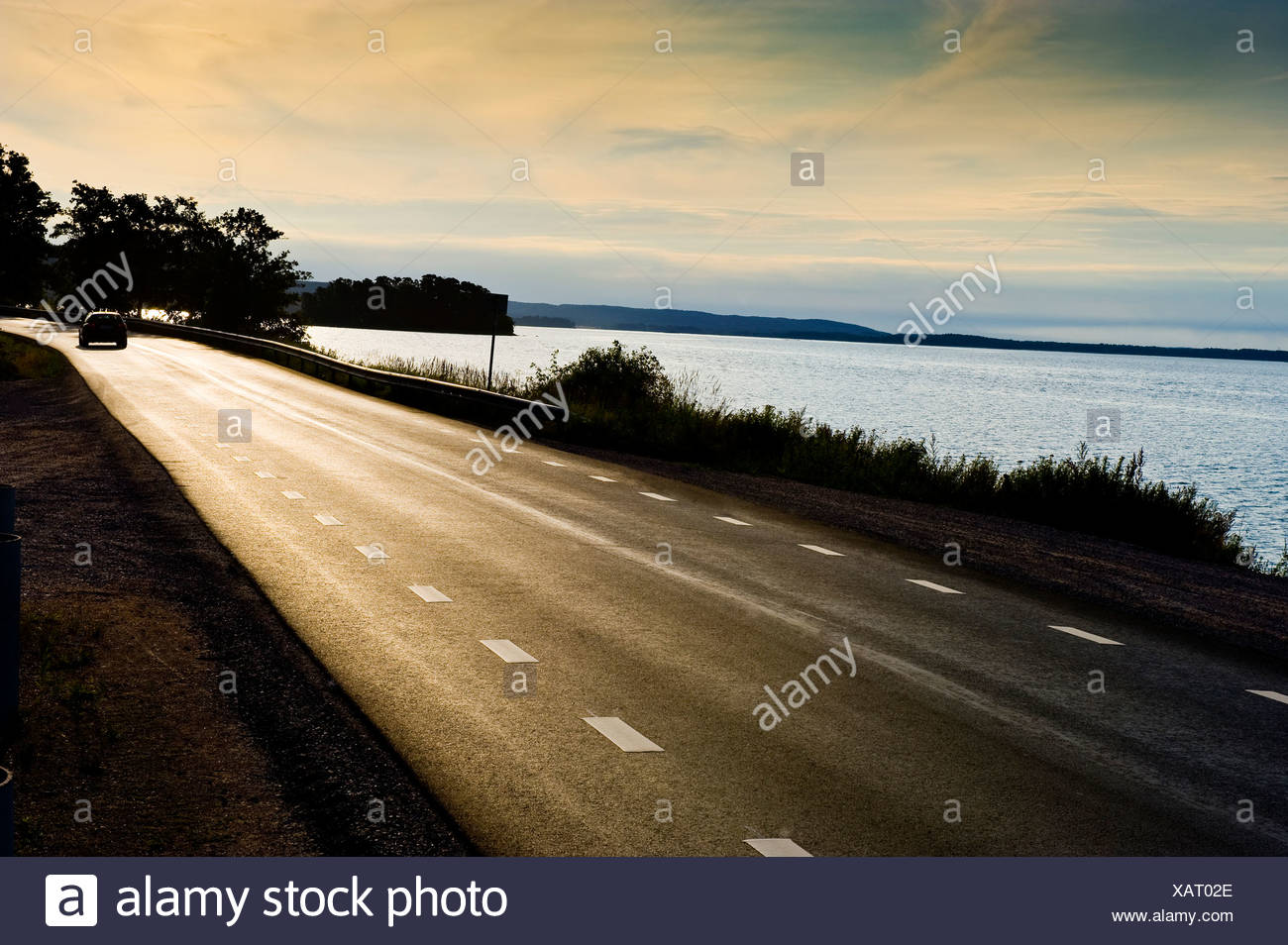 Asphalt road on Bråviken by the sea below cloudy sky at dusk - Stock Image