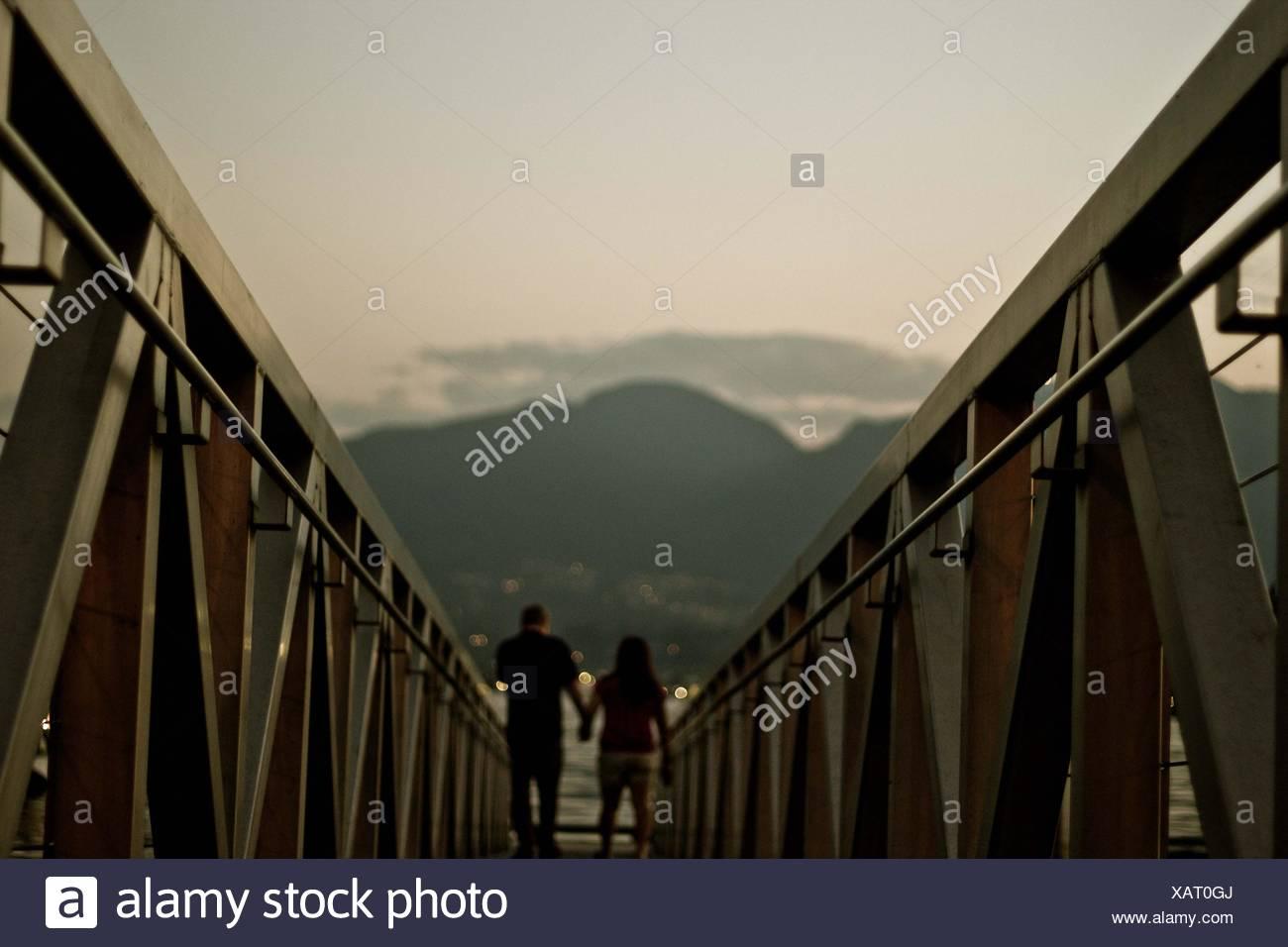 Rear View Of Couple Walking Along Railings - Stock Image
