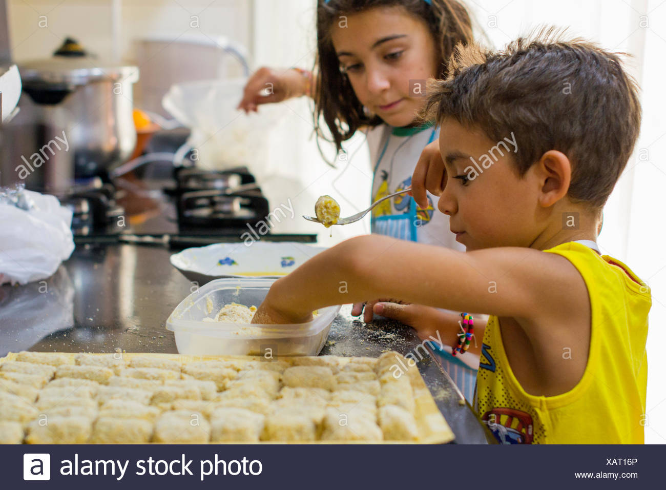 Boy and girl making croquettes in the kitchen - Stock Image