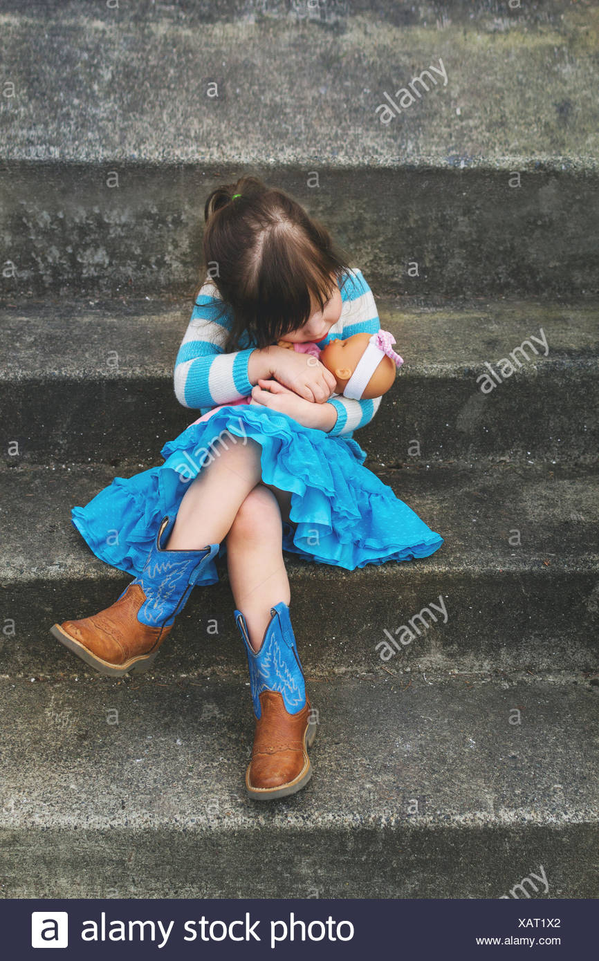 Girl sitting on a step hugging a baby doll - Stock Image