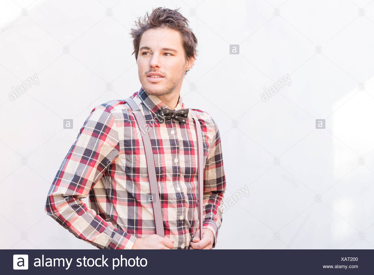 Young man standing in front of wall looking away - Stock Image