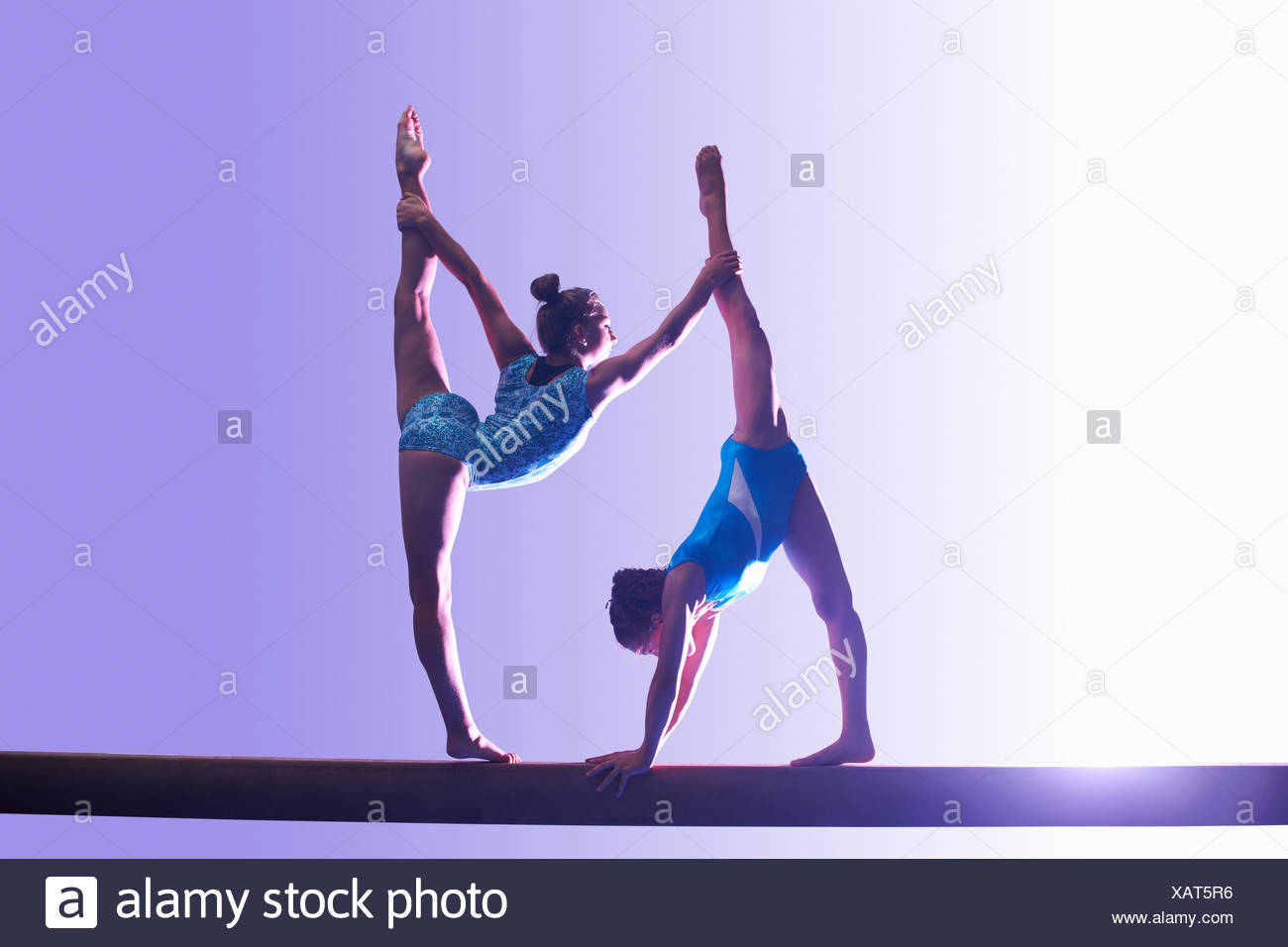 Two young gymnasts performing on balance beam - Stock Image