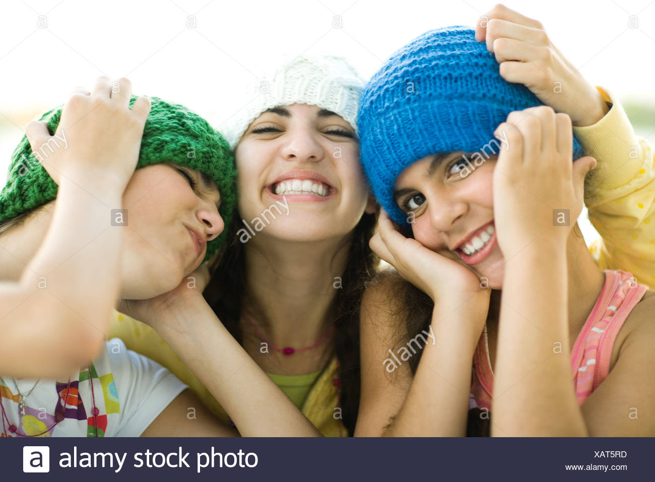 Three young female friends wearing knit hats, smiling - Stock Image