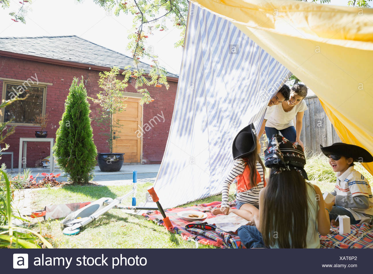 Parents watching children playing pirates in backyard fort - Stock Image