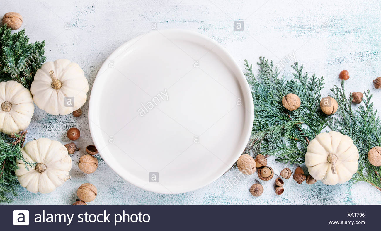 Holiday table decoration with white decorative pumpkins, thuja branches, walnuts, acorns and empty dinner plate over white woode - Stock Image